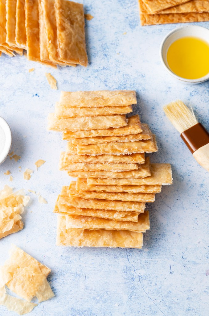 Mille-feuille pastries on a blue backdrop with butter and a pastry brush