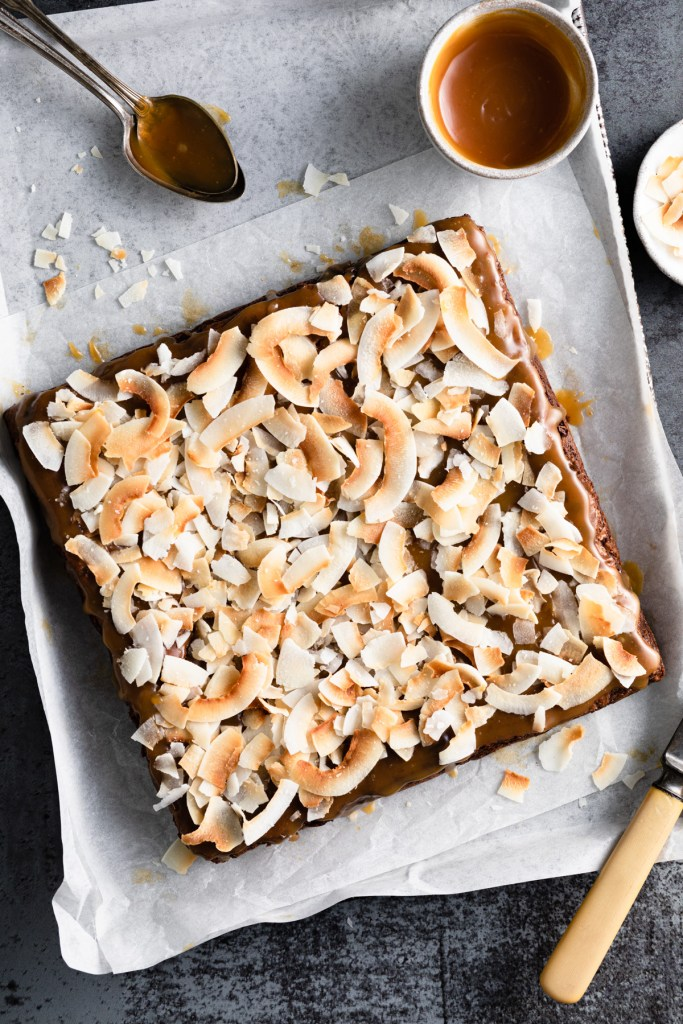 coconut caramel brownies on a pan and parchment