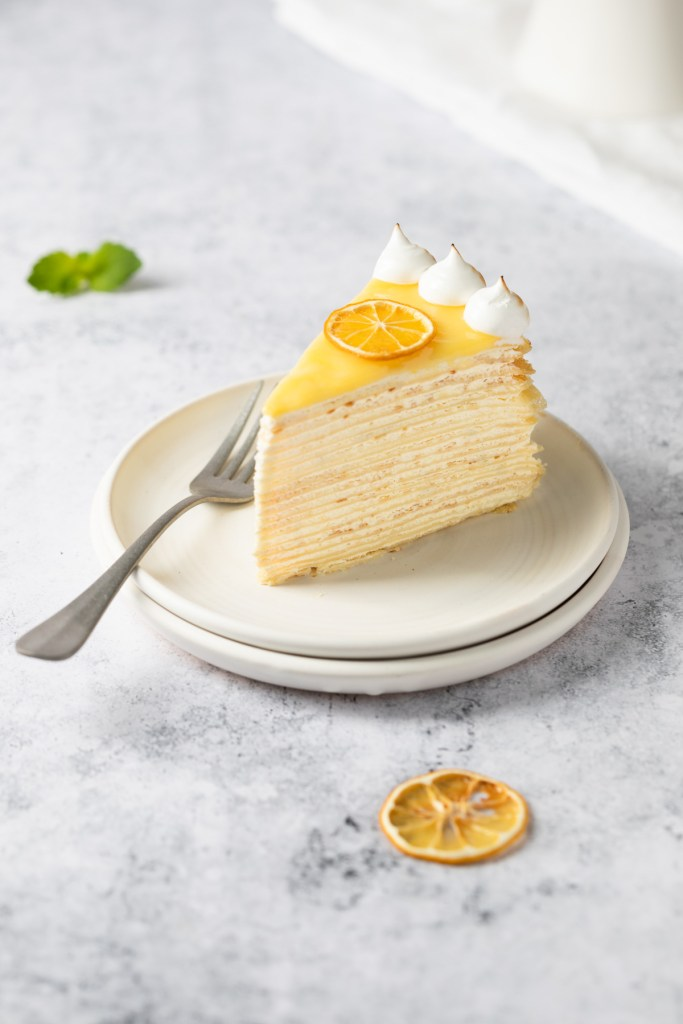 slice of crepe cake topped with lemon curd