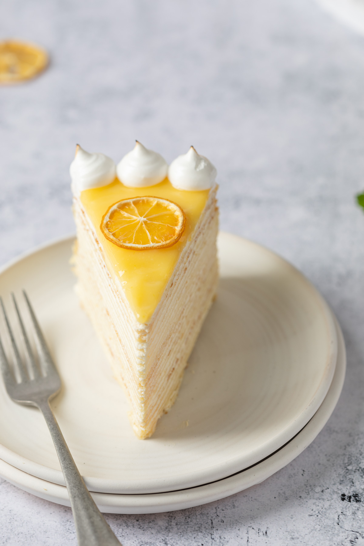 slice of lemon crepe cake with lemon curd and italian meringue