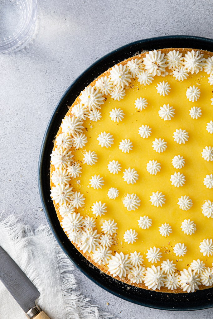 whole lemon mascarpone tart on a blue plate with a knife off to the left