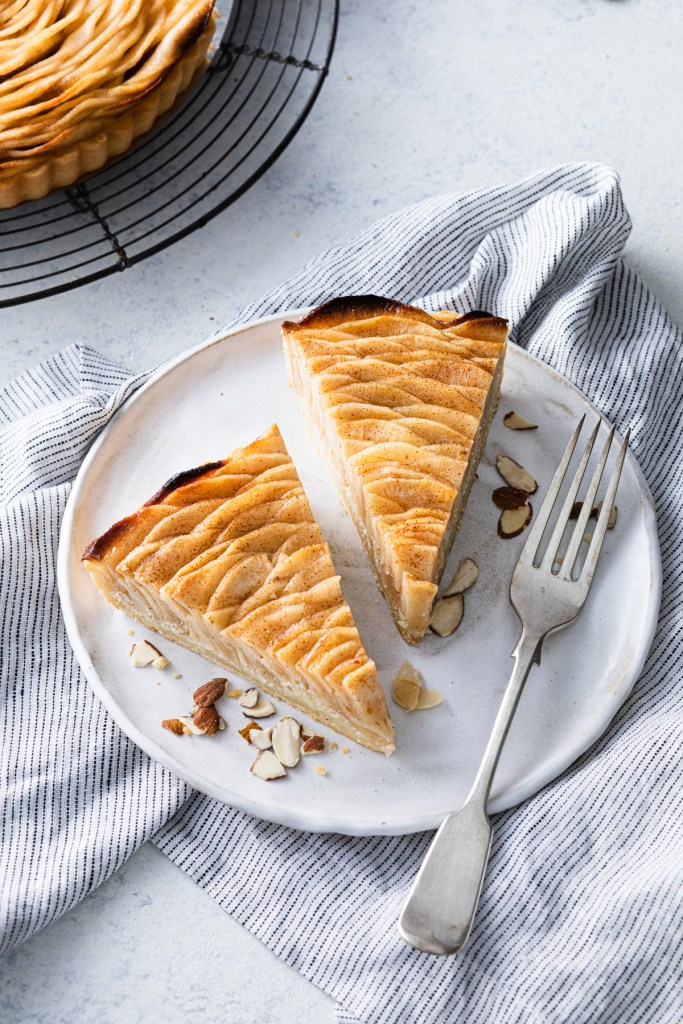 two slice of a french apple tart on a plate with almonds and a fork