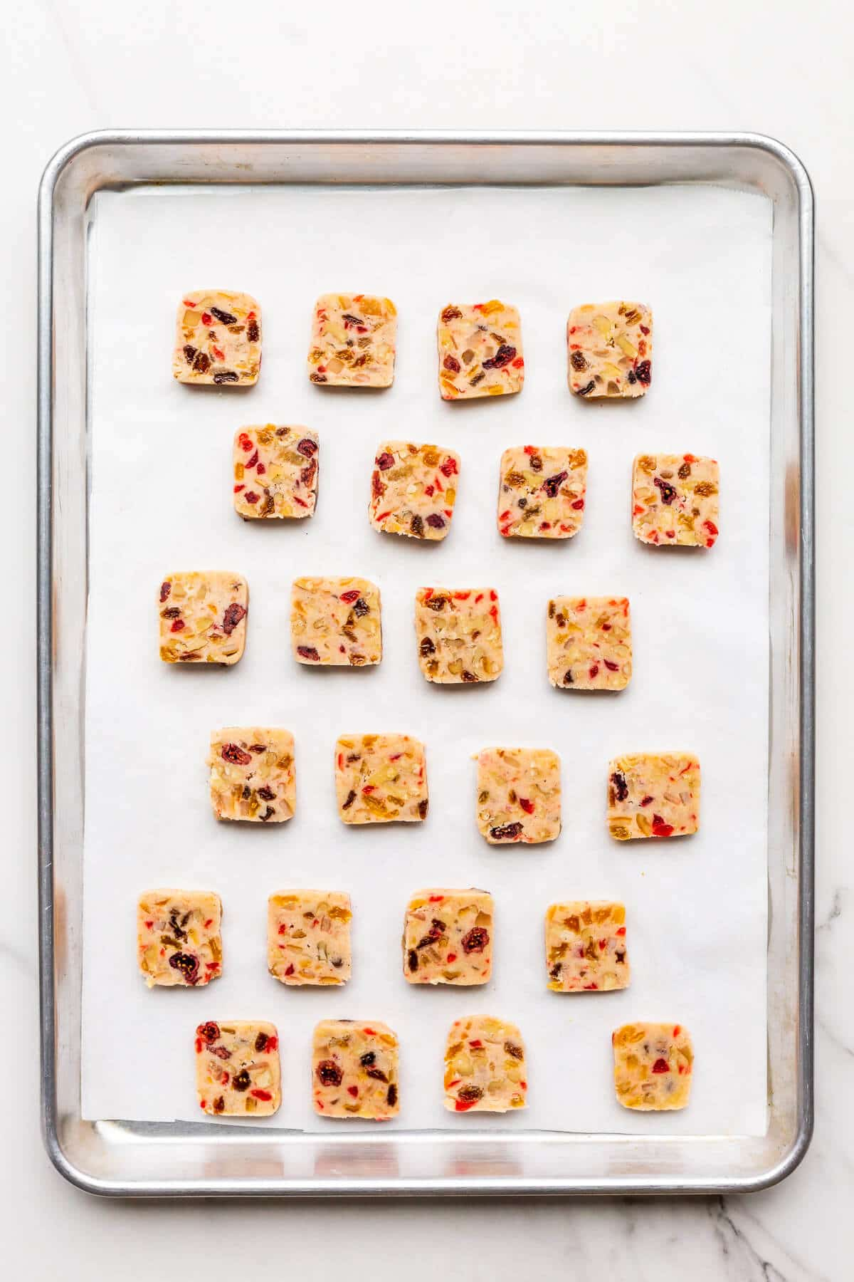 A parchment-lined sheet pan of fruitcake cookies ready to be baked.