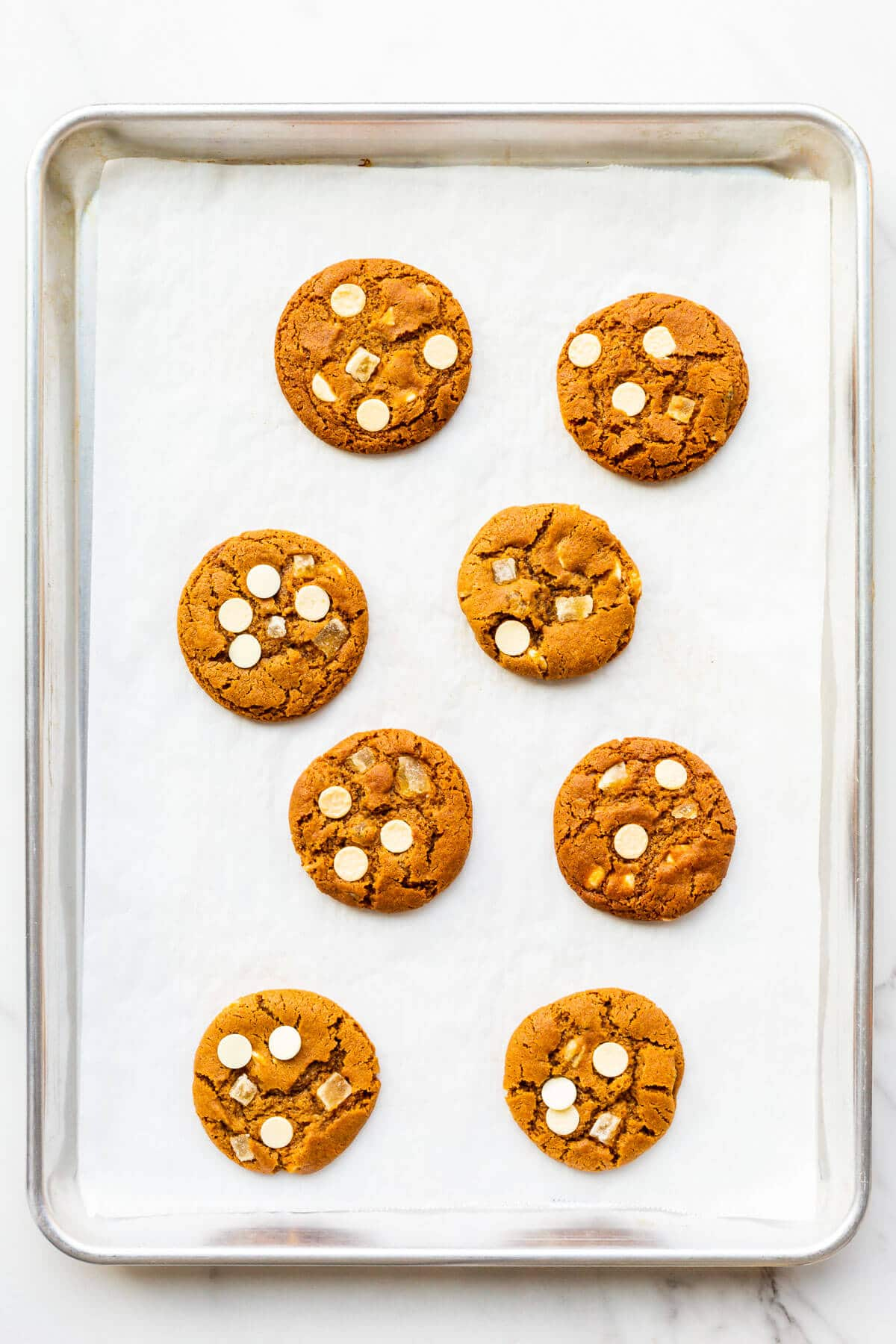 A sheet pan of freshly baked ginger cookies with white chocolate chips and chunks of crystallized ginger.