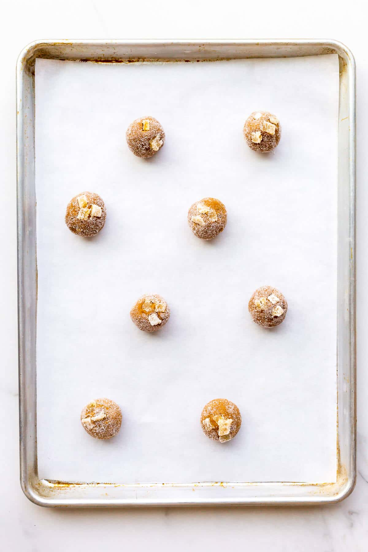 Scoops of ginger cookie dough rolled in granulated sugar before baking on a parchment-lined sheet pan.