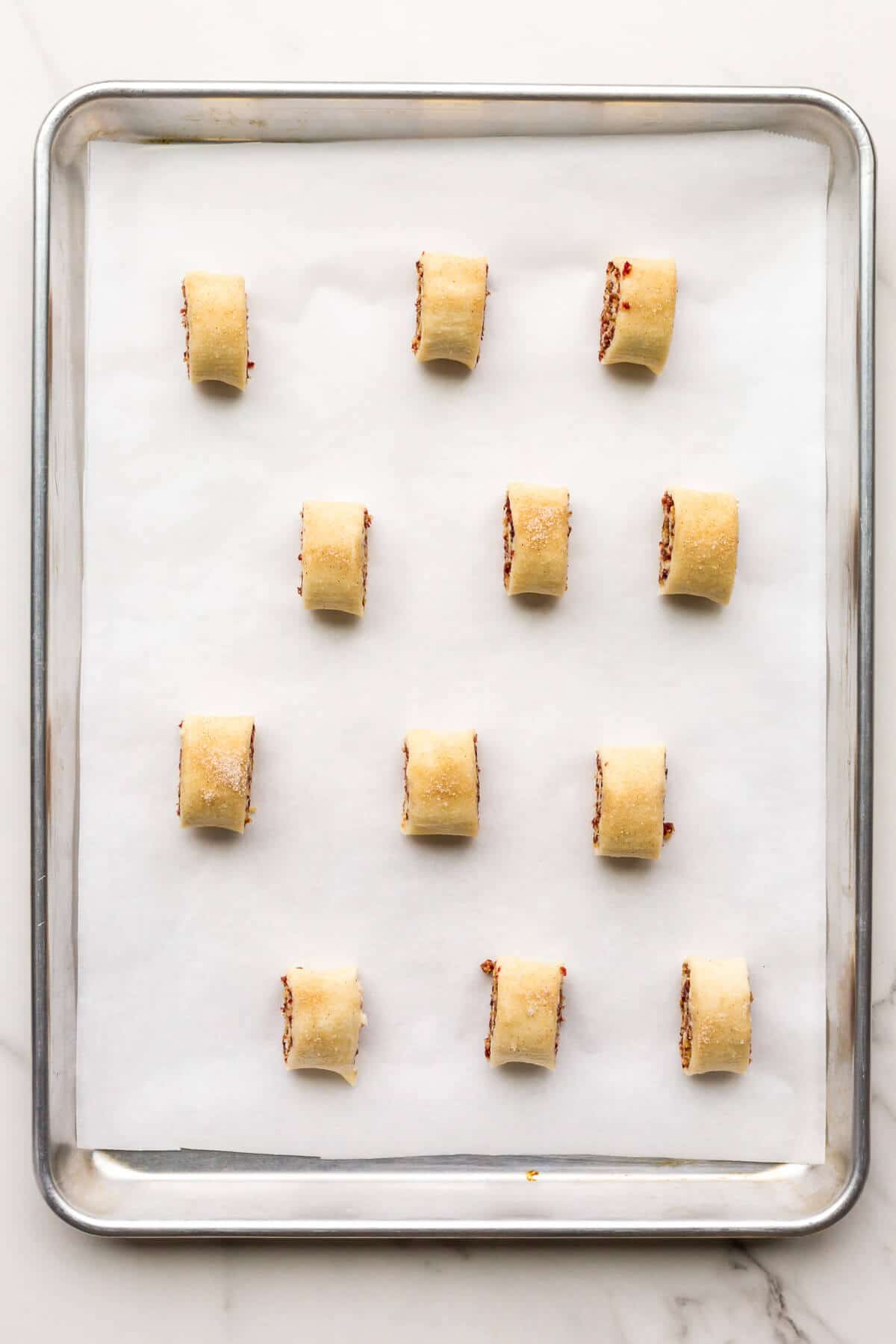 Rugelach before baking on a parchment-lined baking sheet.
