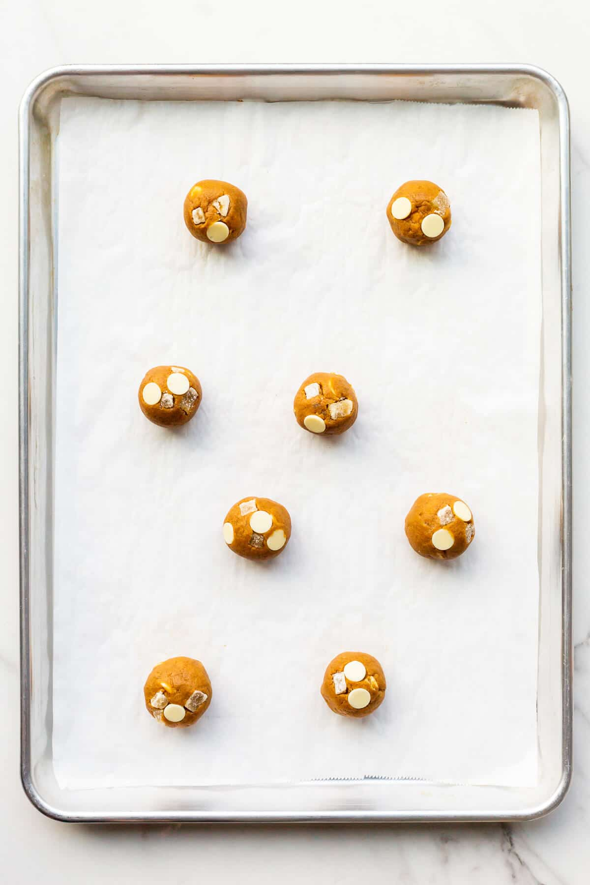 Scoops of ginger cookie dough with white chocolate chips before baking on a parchment-lined sheet pan.