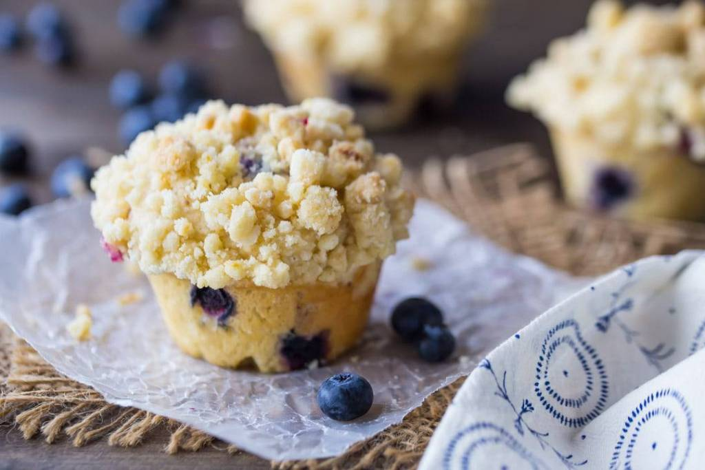 Horizontal image of a homemade blueberry muffin with streusel topping.