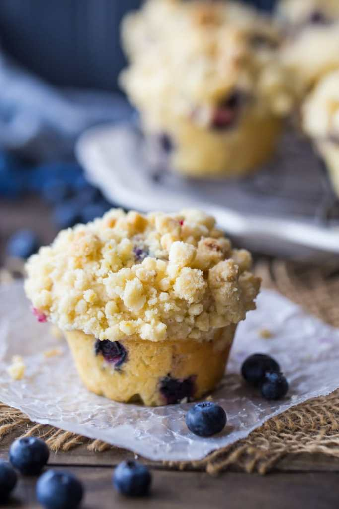 Vertical image of a crumble-topped blueberry muffin on a dark background, with a tray of blueberry muffins behind.