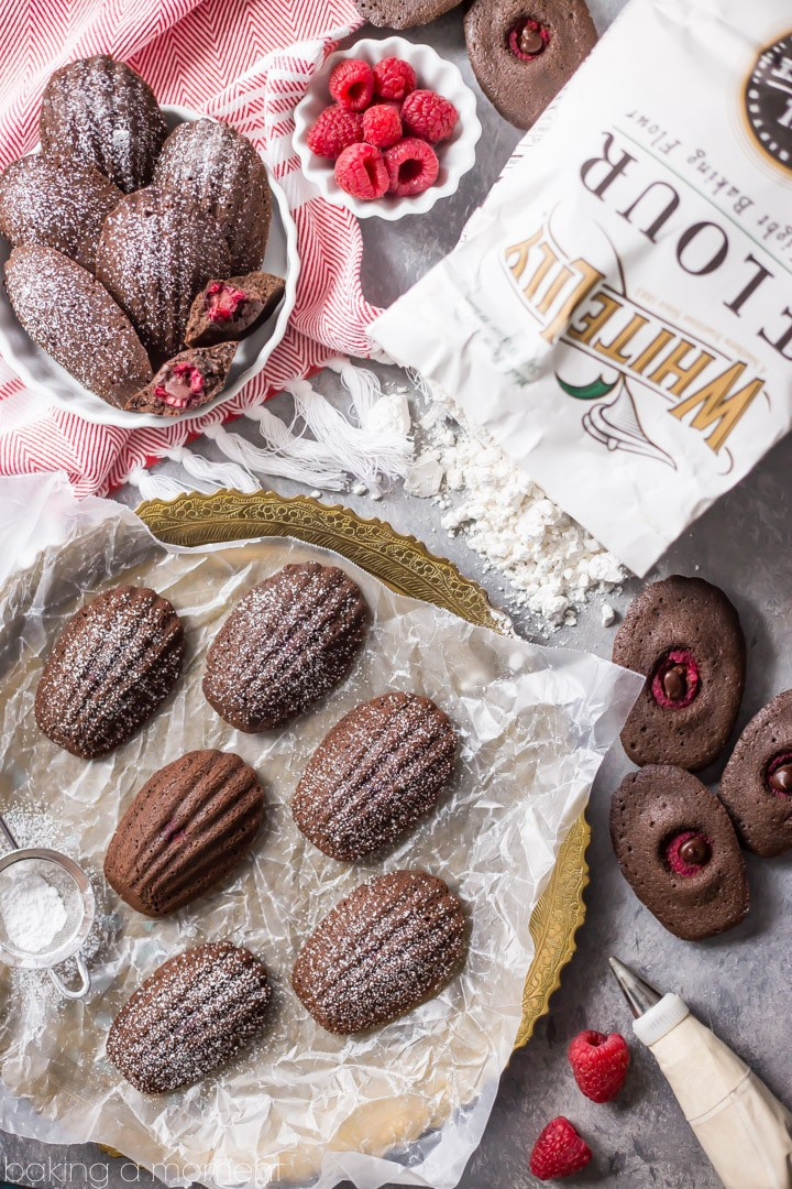 Chocolate Raspberry Madeleines: these little cakes are so perfect for a special occasion! Taste like a cake-y brownie, with a fresh raspberry baked inside. The shell shape couldn't be prettier! #BakeYourPassion #sponsored @whitelilyflour food desserts chocolate