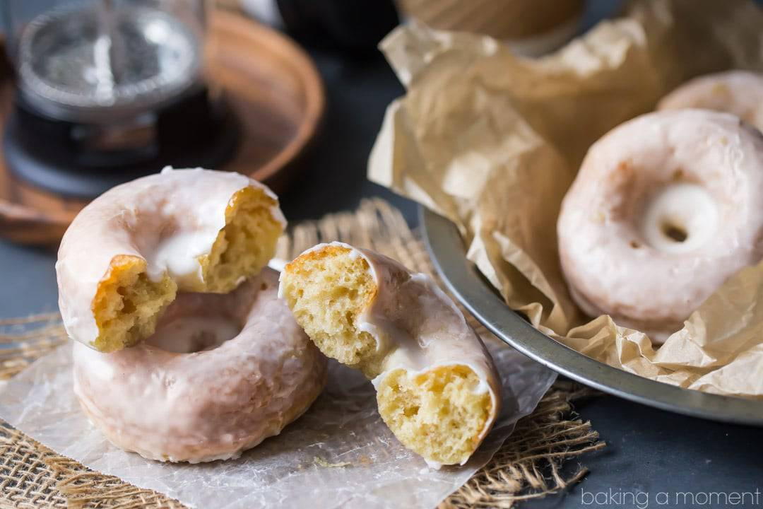 Glazed sour cream cake donuts, with one broken in half.  Coffee pot and coffee cups in the background.