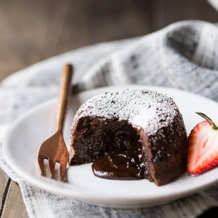 Chocolate Molten Lava Cake On A White Plate With Liquid Spilling From The Center