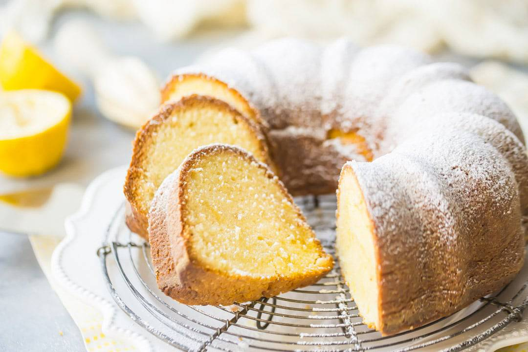 A moist lemon pound bundt cake, dusted with powdered sugar, on a wire cooling rack over a yellow napkin.