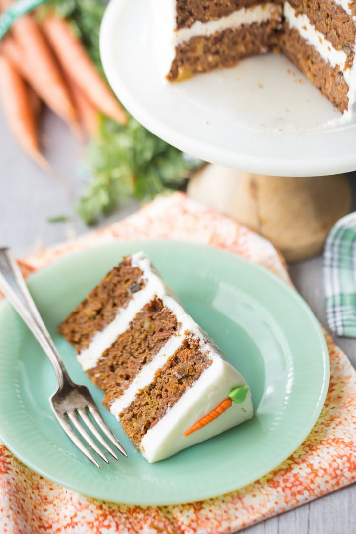Slice of triple-layer carrot cake with cream cheese frosting, on a green plate with fresh carrots in the background