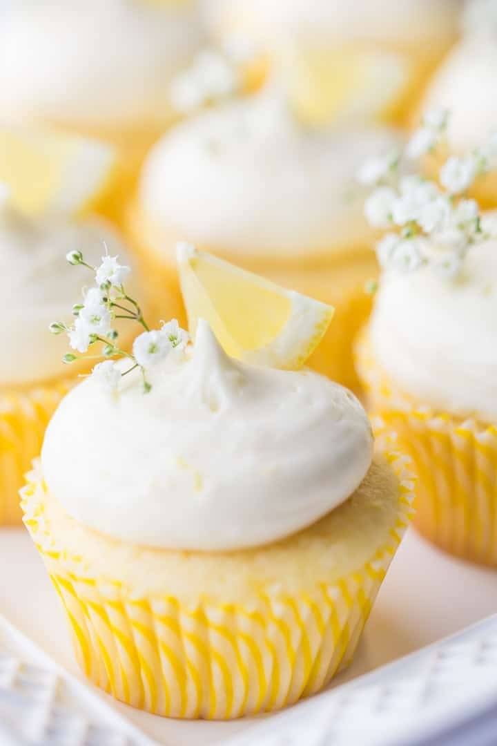 Vertical image of lemon cupcakes with lemon curd filling and lemon cream cheese frosting, garnished with lemon wedges and baby's breath.