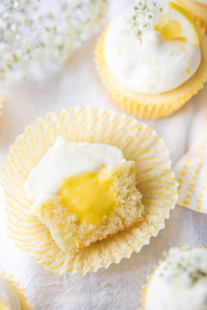 Overhead view of lemon cupcake cut in half, showing lemon curd filling and cream cheese frosting.
