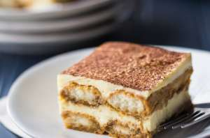 Square image of a slice of tiramisu on a white plate over a dark blue background.