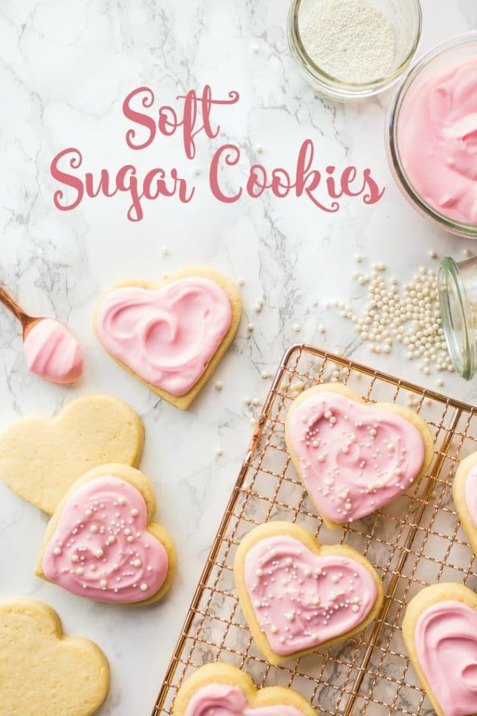 Vertical image of soft rolled sugar cookies on a copper cooling rack, with pink sour cream frosting.