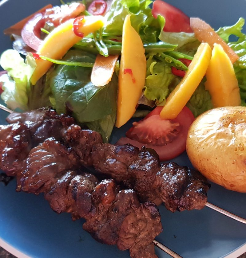 Teriyaki beef skewers with salad and baked potato