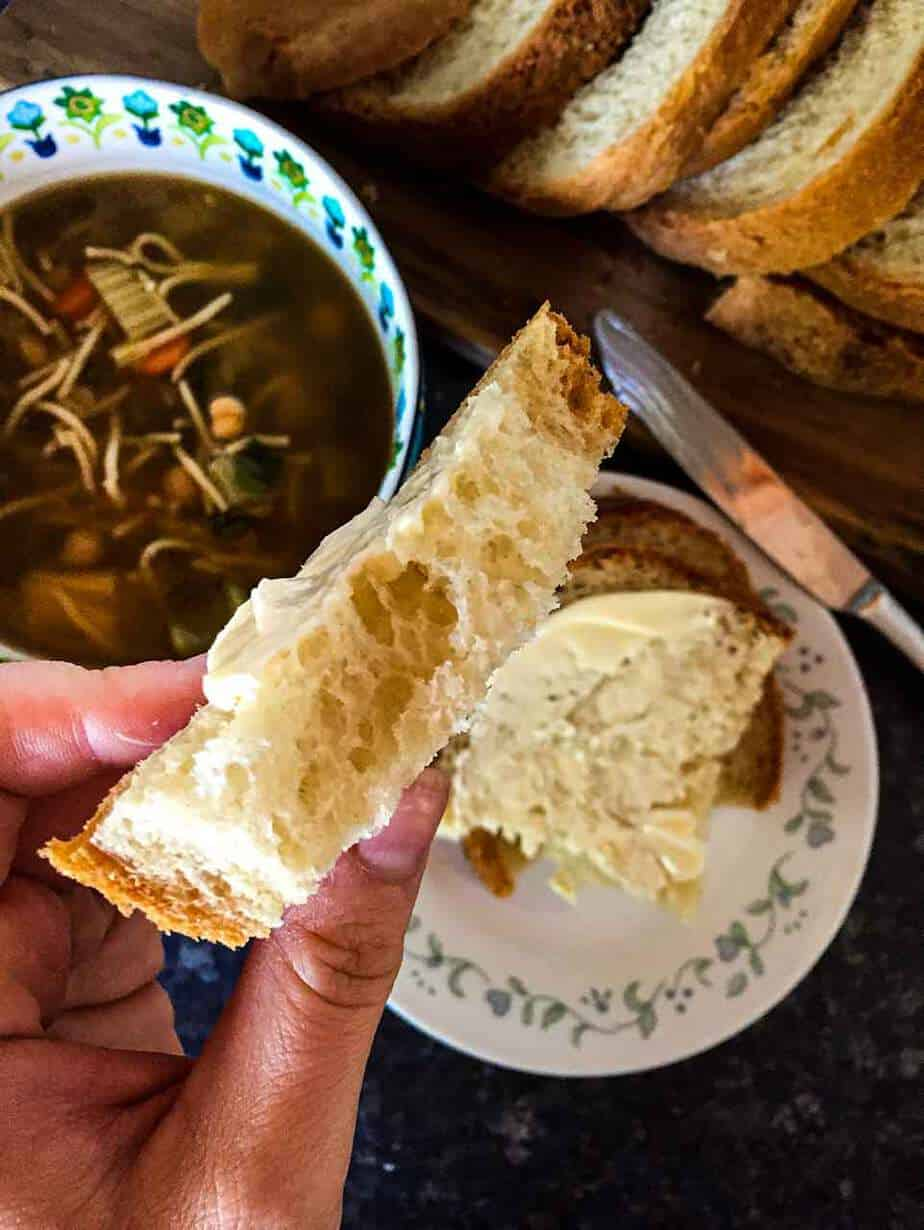 Vegan bread ripped and shown in a hand to show the texture