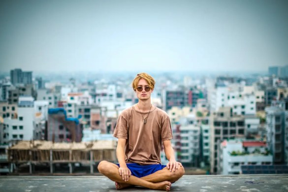 A young man sits in a meditation posture with a city landscape behind him. He may be trying to find his true self by asking Who am I?