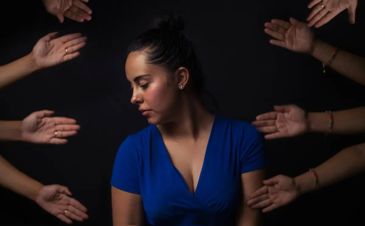 A computer generated image is shown of a woman looking down with a face like she wants to get away with eight hands being pointed in her direction. This image represents the idea that we all can be difficult to deal with.