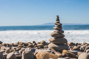 An image of rocks balancing on top of each other is shown in front of a vast backdrop of ocean and sky.