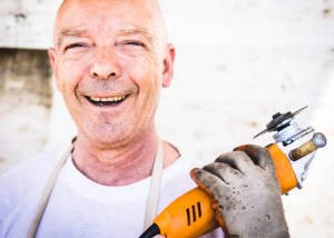 A man is shown smiling holding a power tool in his hand. He has chosen a career path that's perfect for him.