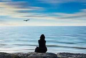 A woman sits on a rock looking out at the sea. Science and spirituality disagree on the cause of the world.