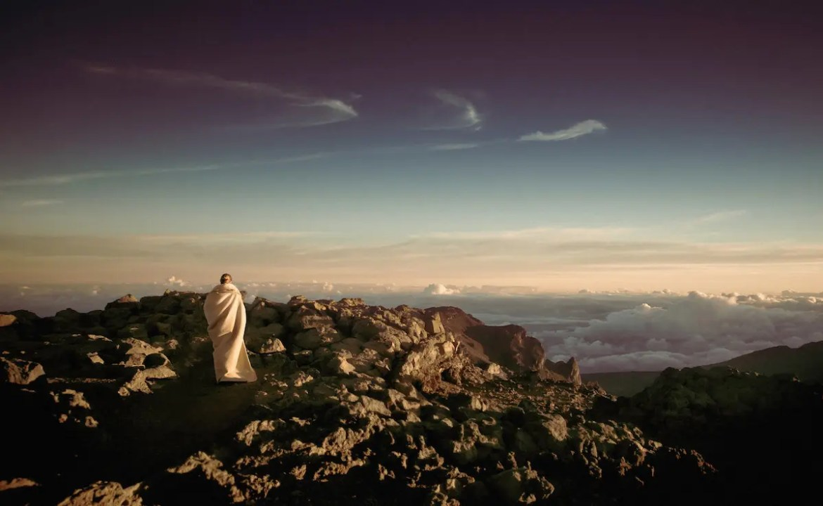 A woman is shown robed in a white blanket looking out over a vast desert. This pictures represents her pondering science and spirituality.