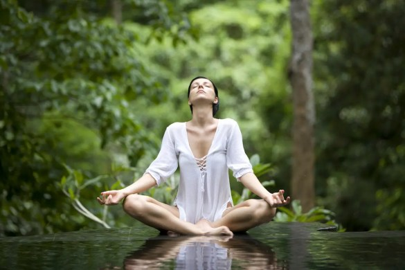 A woman meditates. She is deepening her understanding of the mind body connection.