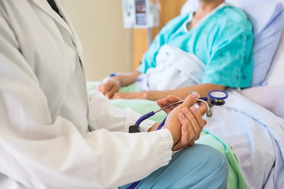 The Power of Expectations: A Doctor sits with their hands together as if they have bad news to tell their patient.