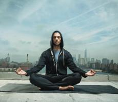 A man meditates against a city backdrop.
