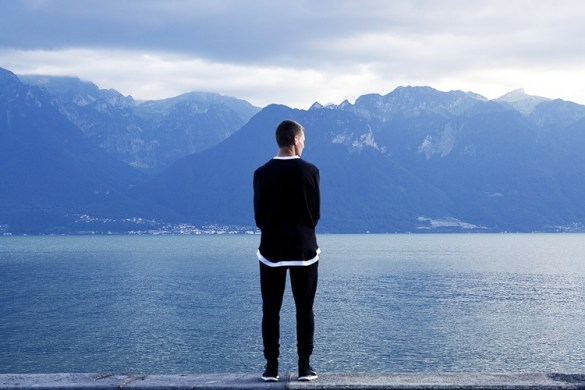 A man looks out over a blue ocean. He ponders failure and what it means.