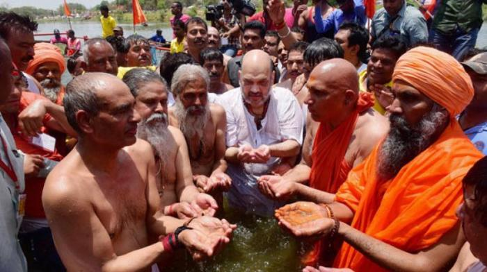 Amit Shah is seen bathing in the Shipra river with the untouchables of India.