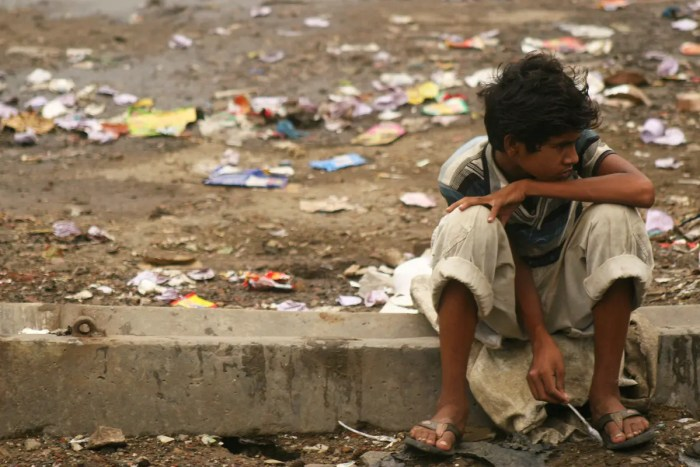 A young boy sits on a street corner surrounded by trash. This is a bleak reality for the untouchables of India.