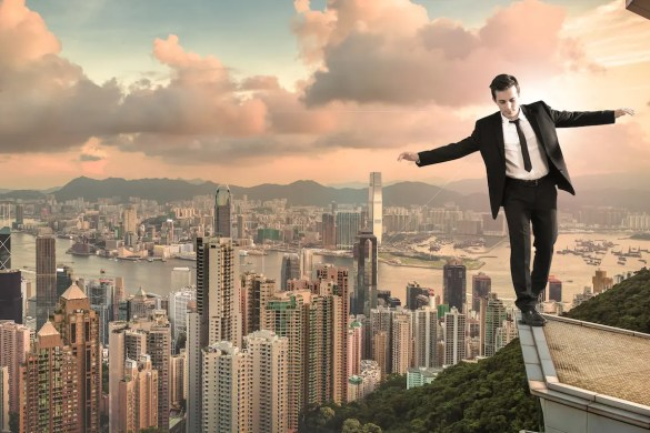Finding Life Balance can often be challenging: A man is shown walking on the edge of a building high above a city in a computer generated picture.