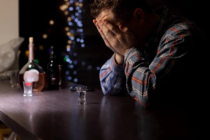 A man sits at a bar with his hands in his face and shot glass in front of him. He is conditioned to respond this way and can stop the habit through neuroplasticity.