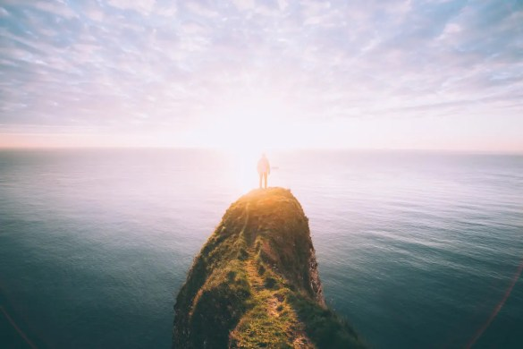 A man stands on a cliff as the sun begins to rise. Asking yourself, 'what am i grateful for?' on an everyday basis can greatly increase your levels of fulfillment.