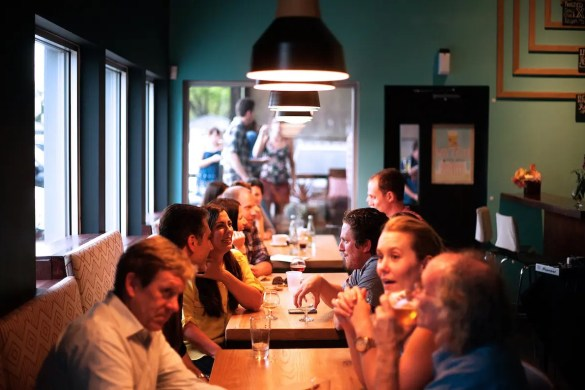 A crowded bar is shown with people talking at dinner. You can enhance your life with dinner conversation questions.