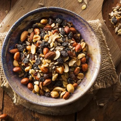 A bowl of homemade trail mix is shown and represents a great alternative to typical snacks. It is one of the featured snacks that fight cancer.