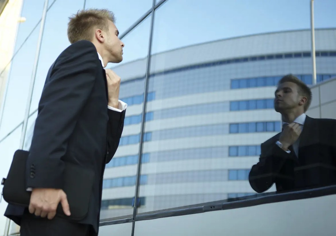 A man wearing a business suit looks into the window of a building to fix his tie. The illusion of self makes us belief we are something that we are not.