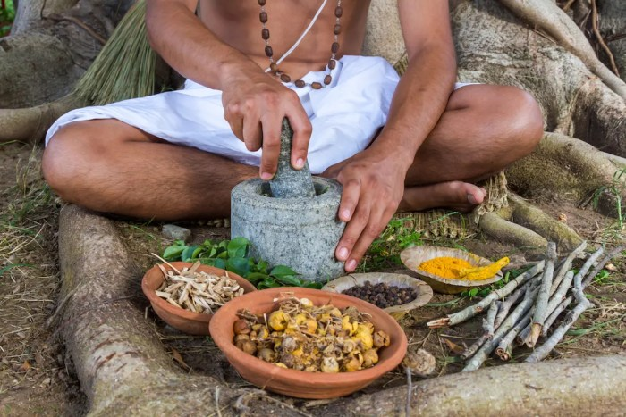 A young man is seen preparing ayurvedic Ayurveda medicine in a traditional manner with a number of different herbs and spices.