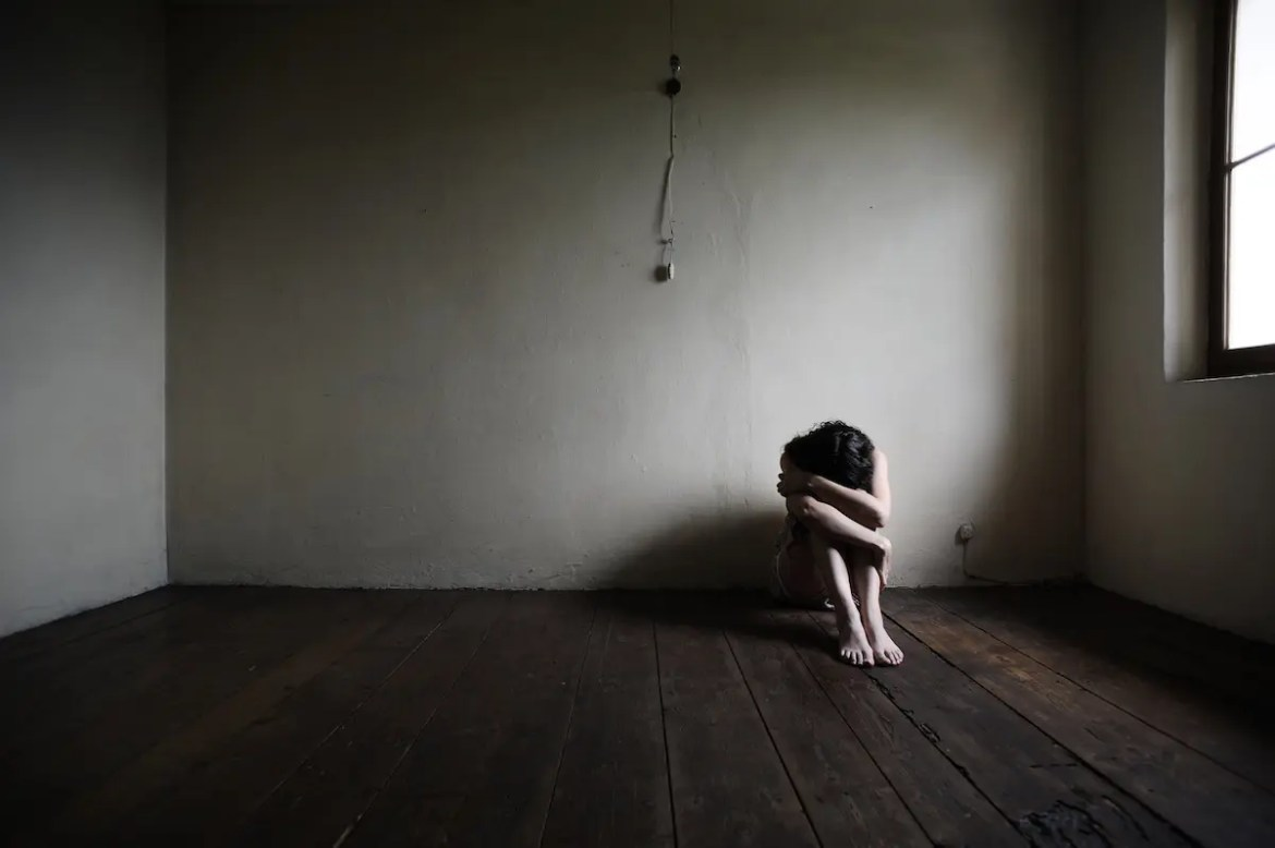 A sad woman sits on the floor in an empty and dark room with her head in her lap and her hands covering her head. Troubling emotions can leave us feeling empty and lonely
