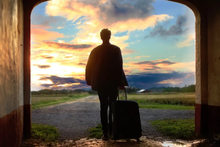 A man with a suitcase looks walks out of open doors as the sunrises. By asking yourself 'What is success?' you can understand that societal ideals often don't lead to happiness.
