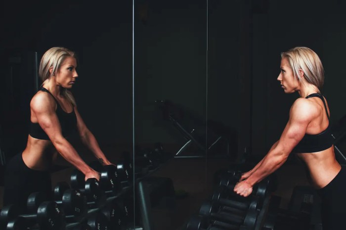 A toned woman is shown working out. She has 2 dumbbells in her and hands and is looking into a mirror with determination. This symbolizes the process of building the decision-making muscle.
