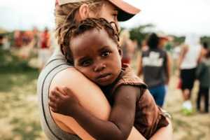A woman from America is shown holding a baby from Africa. Focusing on social good is important for business and personal success. This is why the triple bottom line is such a vital business measuring tool.