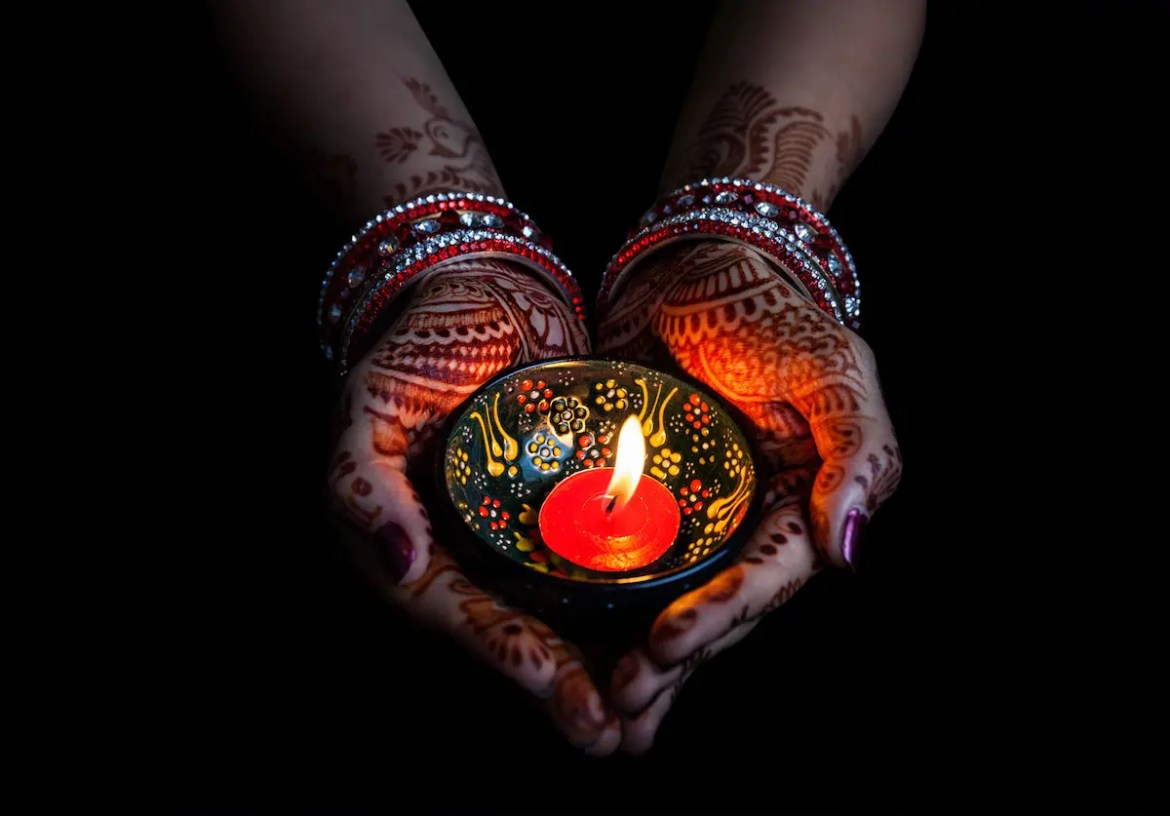 A Woman hands are shown, with henna, holding a lit candle. This image represents Diwali, the Hindu festival of lights.