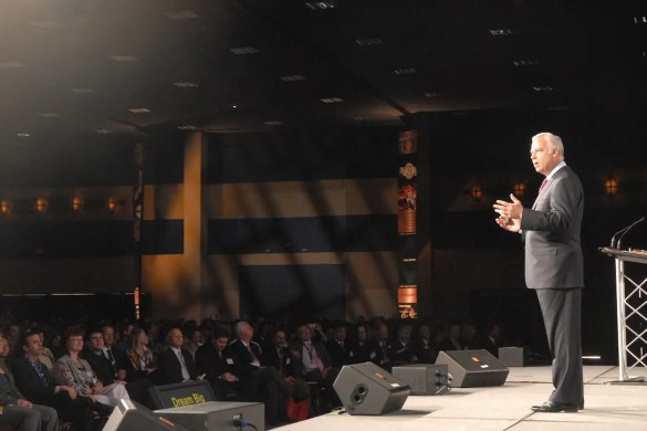 Jack Canfield is shown giving a speech to large audience.