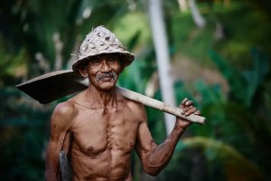 A Costa Rican man is shown smiling with a shovel resting on his shoulder. Nicyoan residents enjoy physically exerting tasks that come with everyday jobs.